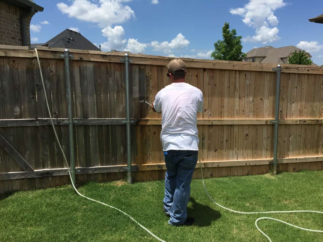 Patriot Stain and Seal cleaning a grey cedar fence getting it ready for stain application.